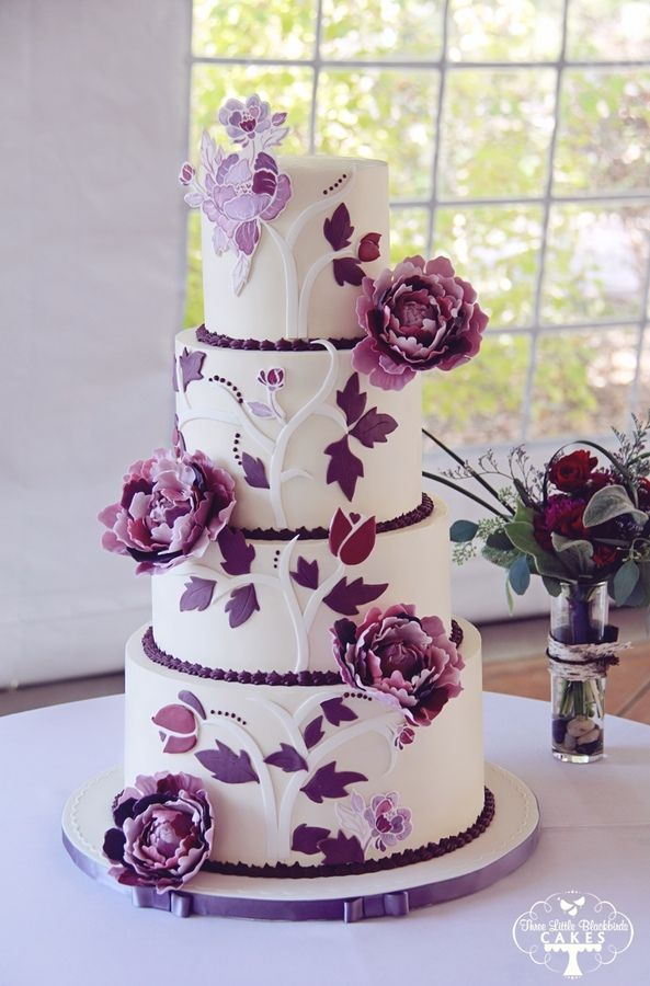 This Fall wedding cake was designed to match the invitation with a mix of 2D and 3D elements. All 4 tiers finished in smooth Swiss Meringue Buttercream and accented with fondant pieces, edible hand painted pieces and sugar peonies in 5 different shades of purple.  Flavors were Triple Berry Vanilla (which has a natural lavender/mauve color and matched the wedding colors), Lovely Lemon (with lemon curd meringue buttercream), and Death by Chocolate Cake with chocolate creme anglaise…