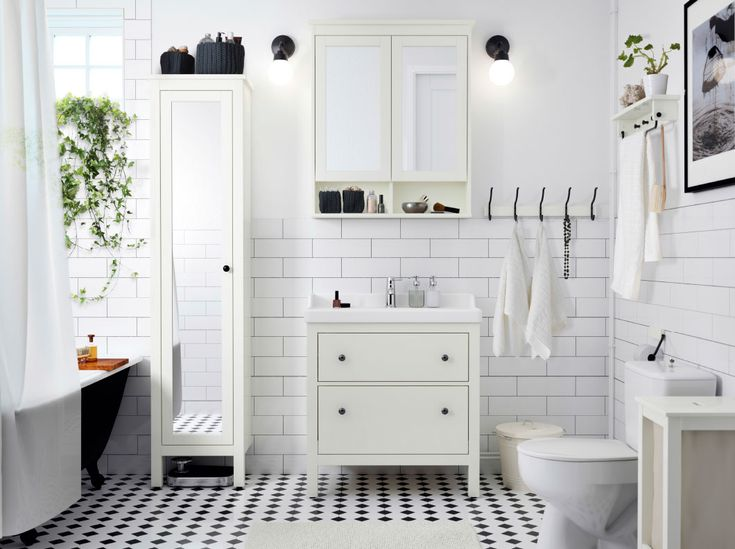 A white bathroom with tiles, wash-stand and high cabinet with mirror door. Combined with a white wash-basin and a wall cabinet with mirror doors.