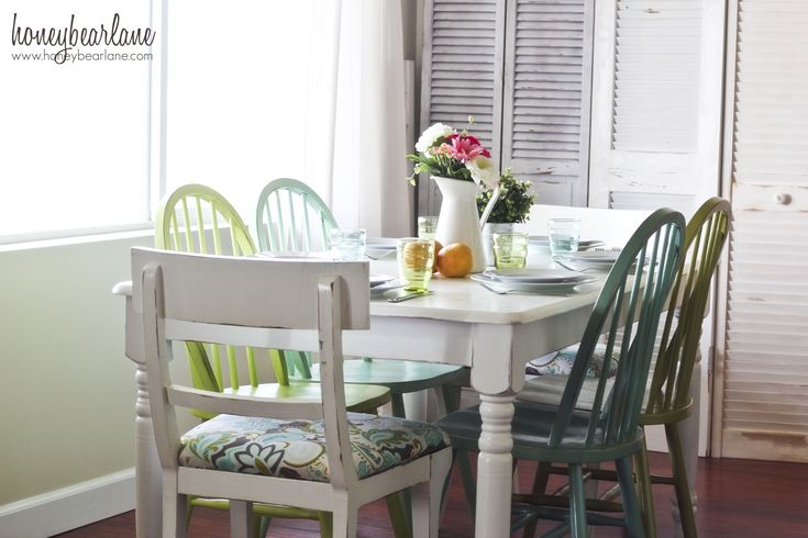 Follow this to see the before and after of this dining table and chairs. Paint  in white, aqua and green was used to unify these mismatched pieces. Windsor wood chairs for the kids and padded chairs for the parents. Such a practical approach to decorating!