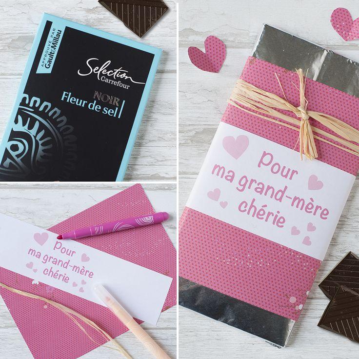 Pour être sur de faire plaisir, suivez notre #DIY plein d'amour 💝 Ôter l'emballage en carton de la tablette de chocolat. Couper un rectangle de 30cm x 14cm dans un joli papier à motifs et entourer la tablette de chocolat avec. Fixer avec du ruban adhésif. Couper une bande de 5,5cm x 29,7cm dans une feuille de papier et écrire le message. Dessiner des cœurs et entourer la plaquette de chocolat avec. Fixer avec un morceau de ruban adhésif. Nouer une petite longueur de fil raphia autour.