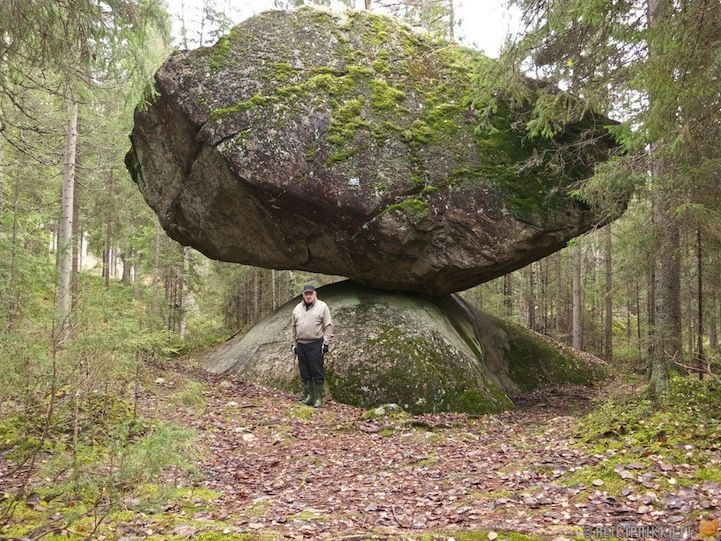 "Certain organic structures in the world leave us all scratching our heads... one such natural wonder is Kummakivi, a geological formation found in the dense forests of Finland. - The mystifying sight is that of a giant rock performing an unbelievable balancing act on a seemingly smooth, curved mound. There is still no scientific explanation for how the rock, whose given name translates as ""strange rock"", has wound up in such a perplexing position??? (1)"