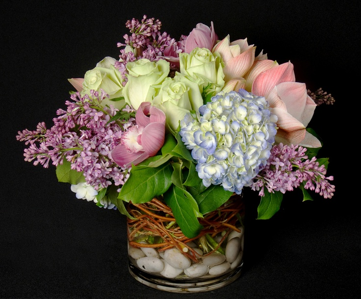 This is a floral arrangement that features roses, cymbidium orchids, hydrangea and lilac in a green, purple and blue color scheme.  See our entire selection at www.starflor.com.  To purchase any of our floral selections, as gifts or décor, please call us at 800.520.8999 or visit our e-commerce portal at www.Starbrightnyc.com. This composition of flowers is generally available for same day delivery in New York City (NYC).  LV041