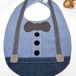 Bavaglino per neonato con applicazione a forma di farfallino e bretelle. Realizzato in stoffa di cotone a quadrettini bianchi e blu e jeans sottile. La stoffa a quadrettini rappresenta la camicia,...
