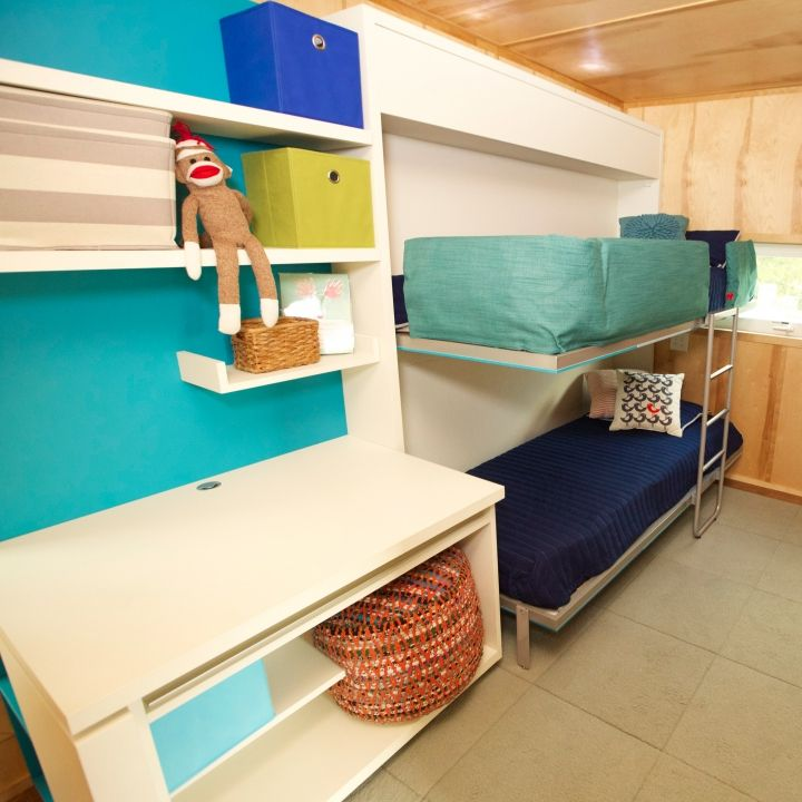 There's plenty of room to play with in the boys' bedroom. Both of the bunk beds fold up into the wall, and the counter converts into two desks for all their academic needs.