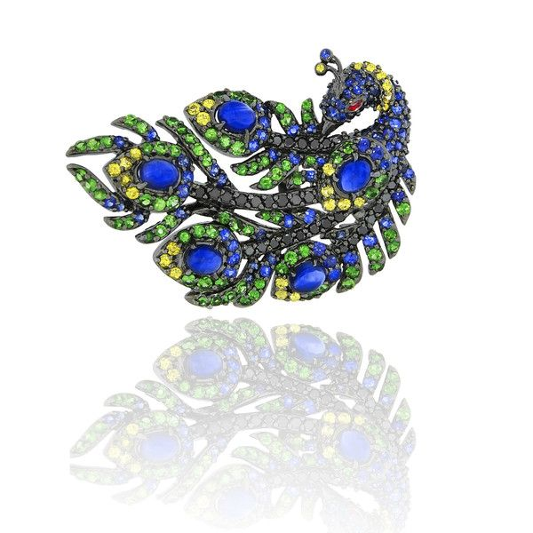 This ring is inspired by the natural beauty of peacock glory feathers. Basic lines made from 18K rhodium gold and set with intensive colorful stones. One ruby of 0.04ct, 27 yellow diamonds constitutes 0.56ct and 32 black diamonds of a total 0.43ct. 76 green garnets of a total 1.50ct and 89 sapphires which weighs 1.55ct. Perfect for day wear as well as for a night out.