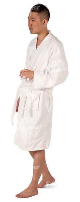 An Asian man in a bathrobe walking