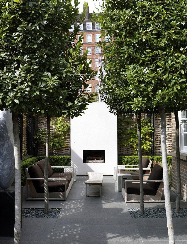 the ultimate outdoor living room in a London city garden, outdoor fireplace, table & seating surrounded by green, stone, & gravel
