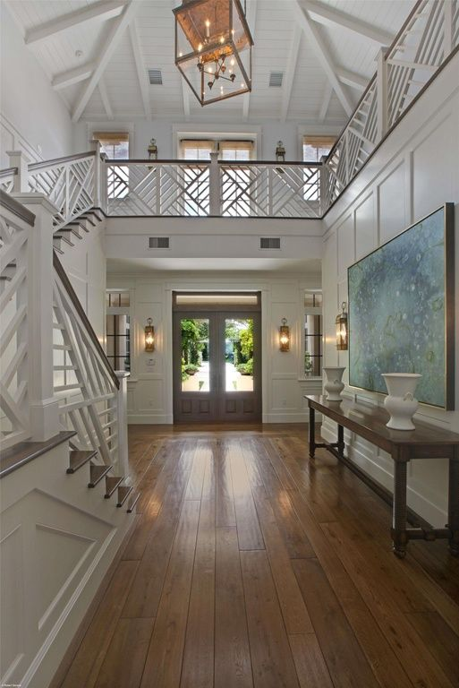 Foyer Layout View : Open entryway with wainscoting and unique staircase