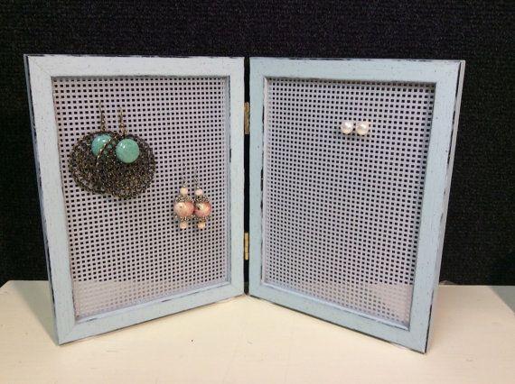Use plastic embroidery canvas encased in picture frame. Add small hooks for hanging earrings with snap-closures.