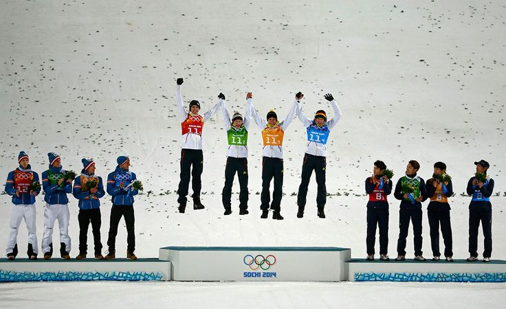 Germany's winning ski jumping team members Andreas Wank, Marinus Kraus, Andreas Wellinger and Severin Freund during the flower ceremony