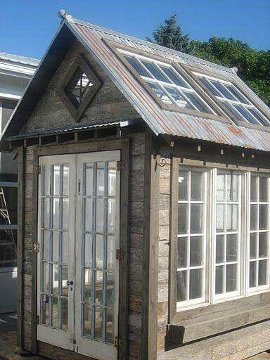 Greenhouse made from old windows and doors and packing crate .