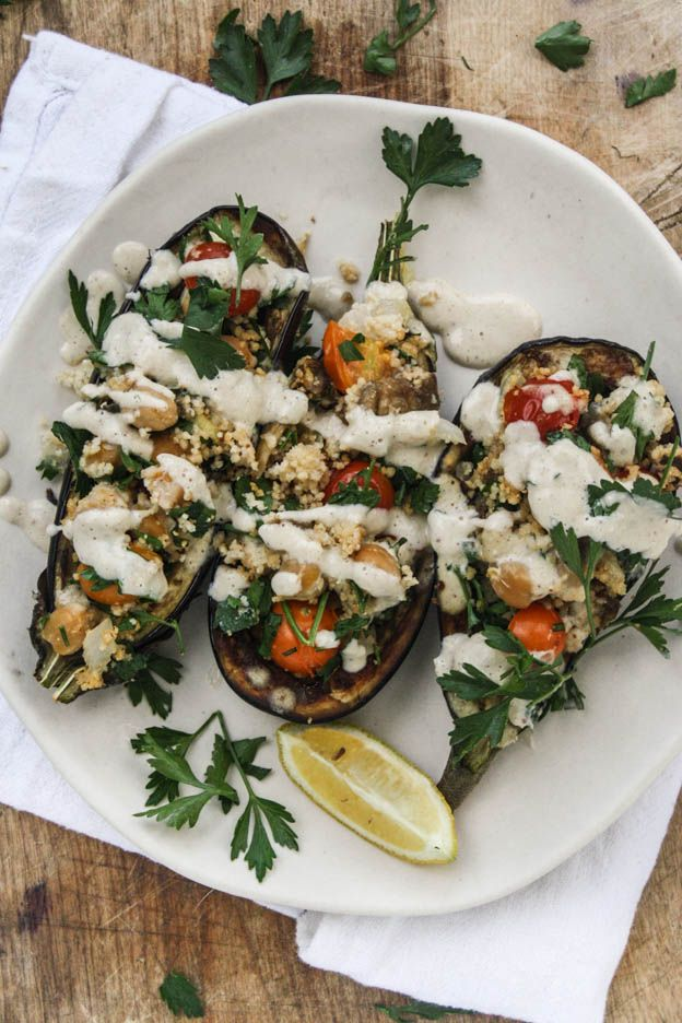 Chickpea stuffed eggplant with couscous and tahini sauce.