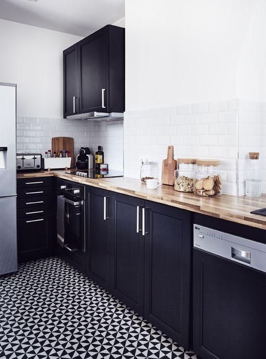 Cocina con paredes blancas y muebles oscuros. Mesada de madera en ...