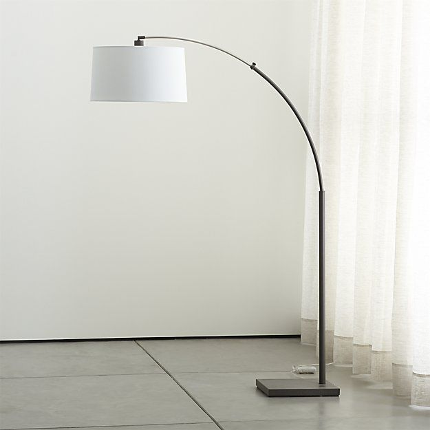 Shop Dexter Arc Floor Lamp with Grey Shade.  Grey on grey lamp arcs overhead light and over-the-top drama.  Soft grey drum shade, finely textured in a cotton blend, suspends from a small profile matte steel base and retractable pole.