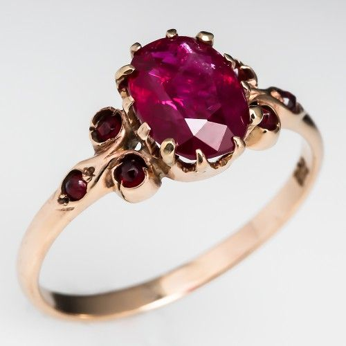Victorian Ruby Ring. This circa 1900 antique ruby ring is centered with a twelve prong set natural oval cut ruby in a nice low profile mounting. Each shoulder is accented with round cut natural almandine garnets. The ring is crafted of solid 14k. c 1900