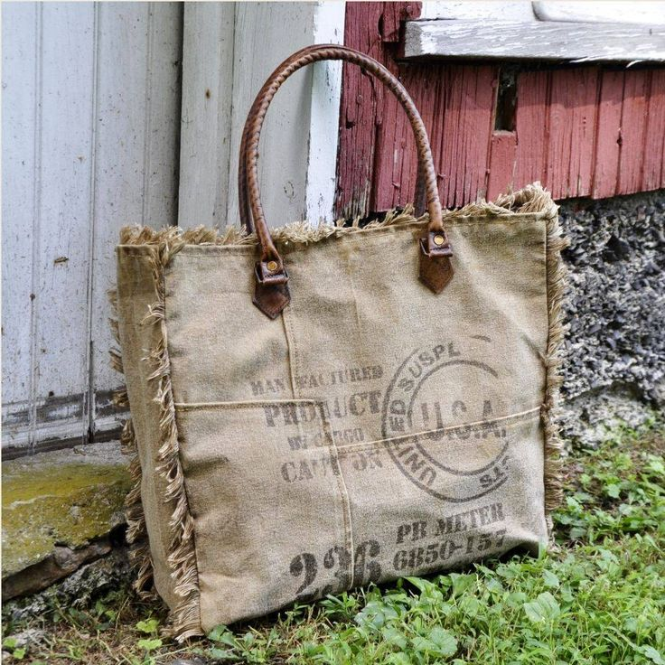 """The Vintage Stamp Fringe Tote features a washed khaki colored tarp with leather handles and fringed seams. Faded graphics add vintage style. This tote is perfect for school, a crafting tote, a beach tote, or an over-sized hand bag! 16""""W x 14""""H x 4""""D. Waste not, is the concept behind these awesome bags from Mona B. Why make new materials when there are interesting and perfectly usable fabrics that can be recycled or upcycled. Mona B's goal is to reduce and reuse some of the worlds waste - or…"""