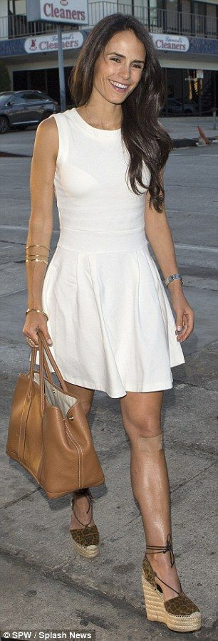 White hot: The actress looked fantastic in a soft pleated white dress that exposed her ton...