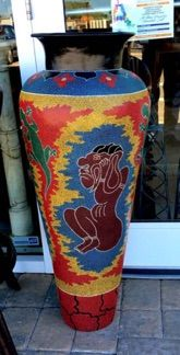 """We've never seen anything like this extra large floor vase decorated with Australian Aboriginal dot painting. Vibrant primary colors surrounding three green lizards and brown human figures all created with thousands of small dots hand painted one by one. Artist unknown. 17"""" diameter  x 41"""" tall."""
