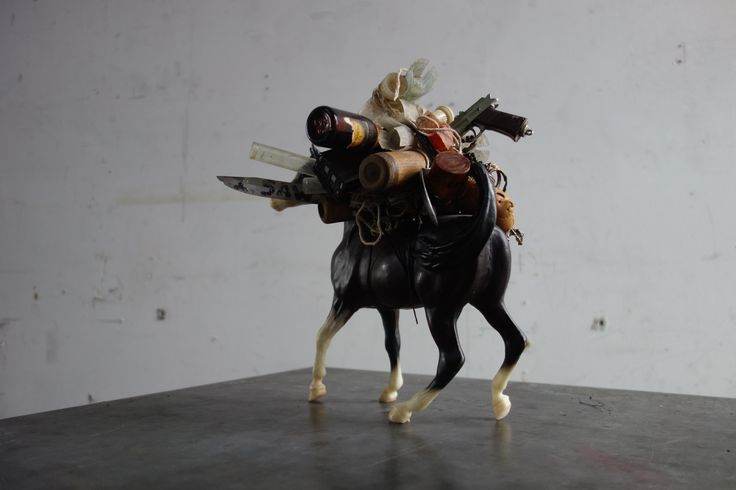 """WarHorse.10"""" high.  holding many means of destruction, including knives, guns, bullets and clubs."""