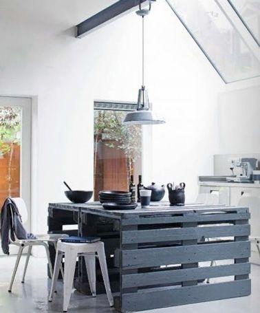 Un îlot de cuisine au ton bleu nuit qui sert à la fois de plan de travail supplémentaire, et de grande table pour un repas convivial en famille.