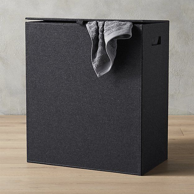 Shop charcoal felt laundry hamper.   Boutique hotel-style hamper is sturdy in a charcoal menswear wool felt blend with light grey double topstitching at the corner seams.  Fabric lined with neat snap-out drawstring bag; open handles air it out.