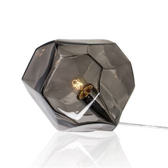 The cool Rock table lamp is designed by Tess Palm for the Swedish brand Globen Lighting. The lamp is made of faceted, angular and unequal sided glass with details in metal. Place the lamp on a sideboard or maybe on the windowsill