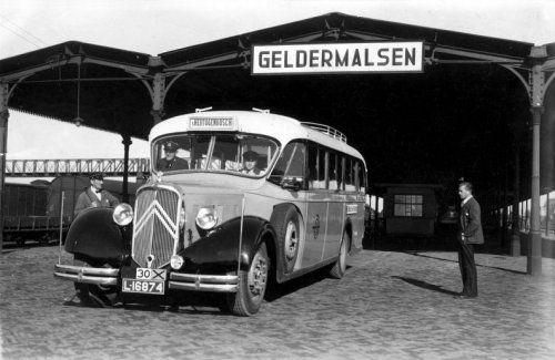 De (Citroën) autobus van de ATO naar 's Hertogenbosch op het station van Geldermalsen, 1935 of eerder, gereedstaand voor vertrek. Een man kijkt toe.
