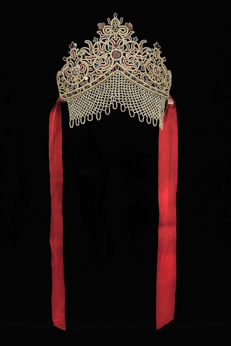 Decoration for a woman's holiday headdress (kokoshnik) beadwork Probably 19th century DIMENSIONS 27.3 x 32.7 cm (10 3/4 x 12 7/8 in.) Gilt-silver wire frame, colored glass beads and spangles embroidered on stiffened paper ground. Beaded veil at base. Red silk ties at sides. Unembroidered ground cut away.