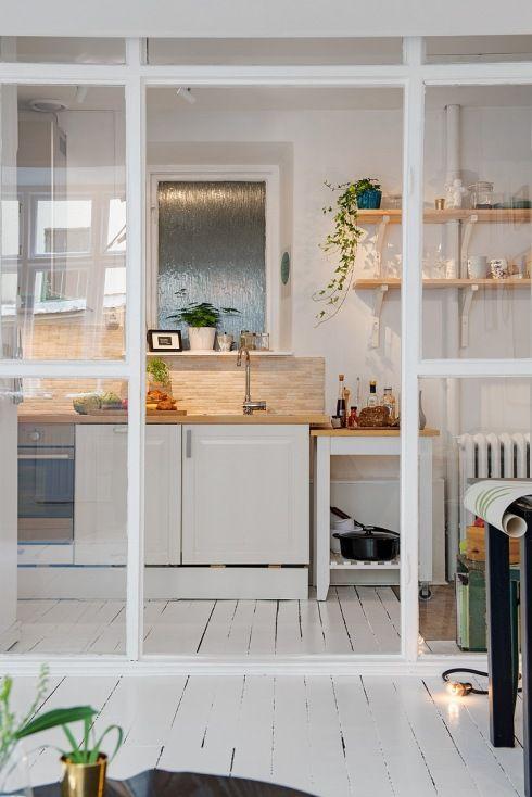 Zdjęcie:  kuchnia we wnęce oddzielona od szalonu przeszkloną ścianką w drewnianych białych ramach