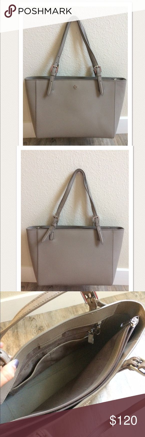 """$245 Tory Burch Small 'York Buckle Tote' in Gray High end department store customer return. Retails for $245 + tax  Very pretty gray Silver tone hardware Main center zip  Measures approximately: total length across 15.5"""" inside depth 8.75""""  Normal signs of wear and light marks on the leather. A a few small spots on the bottoms and front. A small discolored patch under the bottom. Normal wear on inside lining. The straps have some peeling/wear on the leather. Refer to photos. PRICED TO SELL…"""
