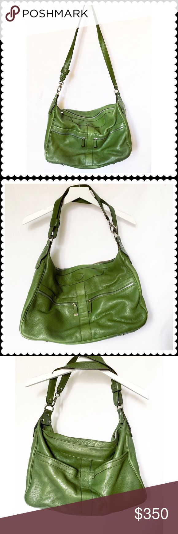 """Tod's large shoulder bag in green tumbled leather Tod's large green shoulder bag in tumbled leather. Strap can be used as long or short as the photos. Canvas lined. Two zipper pockets in front and two open pockets in the back. Also one zipper pocket and two open pockets inside. Gently used with some scuffing on the bottom corners as photo. Sizes are approximately 12"""" high/16.5"""" wide/6"""" thick. shoulder strap Is about 34.5""""long. The strap metal clip got broken and replaced with a stronger one…"""