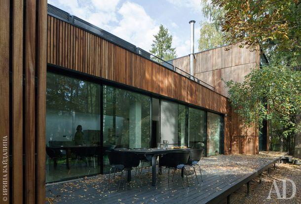 Раздвижная стеклянная стена — прозрачная граница между интерьером гостиной и окружающей природой. Стулья по дизайну Рона Арада снаружи, как ивнутри, черные, в цвет досок натеррасе.