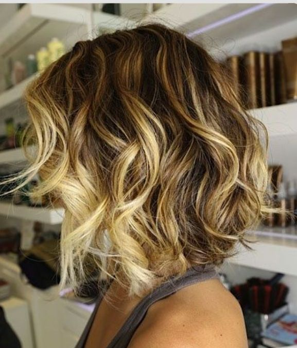 Short, slightly a-symmetrical cut with dramatic chocolate base and golden blonde balayaged highlights