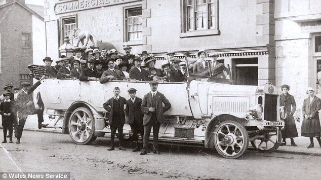 Holiday-goers at Rhyl sit on wooden benches in a charabanc, c.late 1910s-early 20s