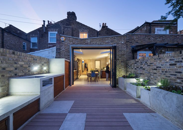 Studio Gil used a combination of exposed concrete and reclaimed iroko wood to unite the interior of this extension to a Victorian terraced house in east London with its redeveloped garden.