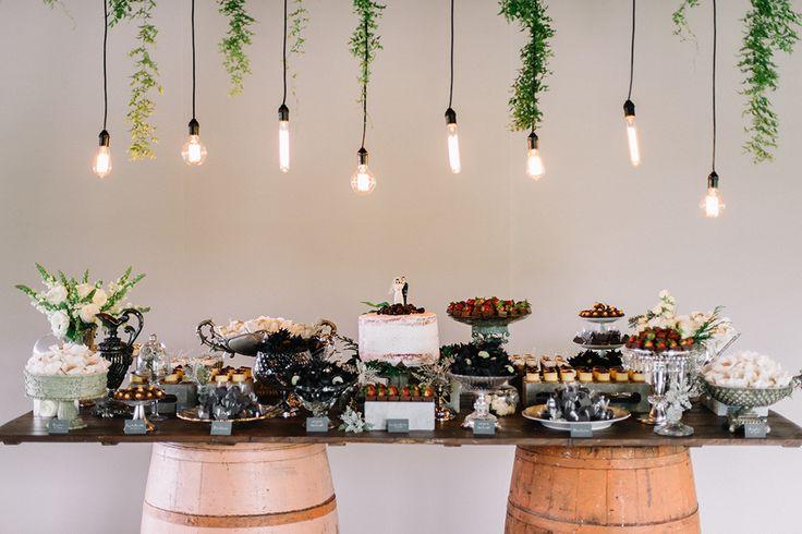 Mesa de doces feita com tonéis de madeira e iluminação com lâmpadas vintage diferentes.
