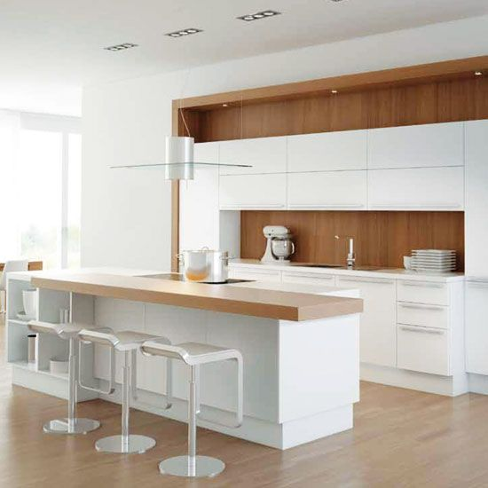 White kitchen with walnut veneer splashback, wood flooring, white island unit and wooden worktop