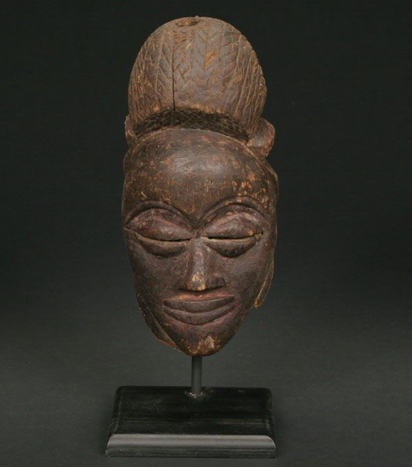 An old Punu mask; Punu or related peoples, Gabon and Congo-Brazzaville; Ogowe River complex. The mask with high sugar-bun coif, and rounded female face with swollen eyes. The surface appears to have been stained in various colors of black and reds over its long period of traditional use. Fine aged surface.  Provenance: A private NY collection. H. 12 1/2""