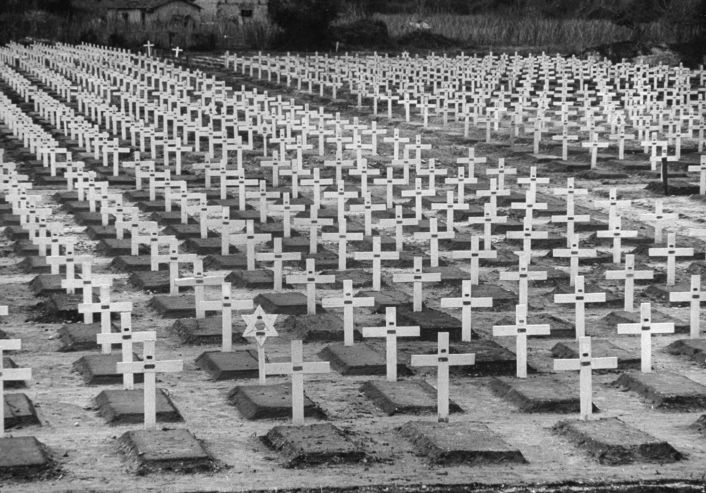 Caption from LIFE. American cemetery on the beachhead is neat and bare. Little metal tags on white crosses bear name and rank of the dead. An occasional Star of David stands among the rows of crosses placed there by U.S. Army's conscientious Graves Registration Service.