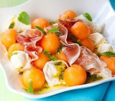 На тарелку выложите листья салата, сверху нарезанную небольшими кусочками дыню, тонко нарезанную ветчину, раскрошенный козий сыр, кедровые орешки и базилик.