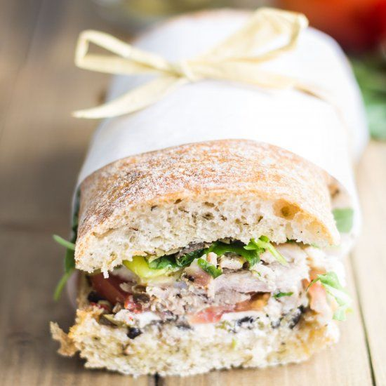 The best picnic sandwich ever! Made with roast chicken, olive tapenade, goat cheese, & sweet pepperoncini, then pressed to perfection!
