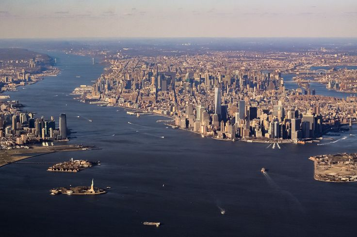 Aerial view of the New York and the Island of Manhattan with the Hudson river to the left. Over 1.6 million people call the Island of Manhattan home. You can see the statue of liberty in the foreground on Liberty island. New York, USA
