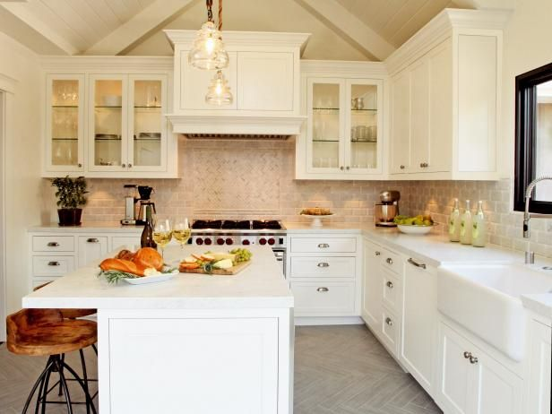 Designer Christopher Grubb combines white cabinetry, stainless steel, and rustic touches to create an farmhouse kitchen. See it on HGTV.com.