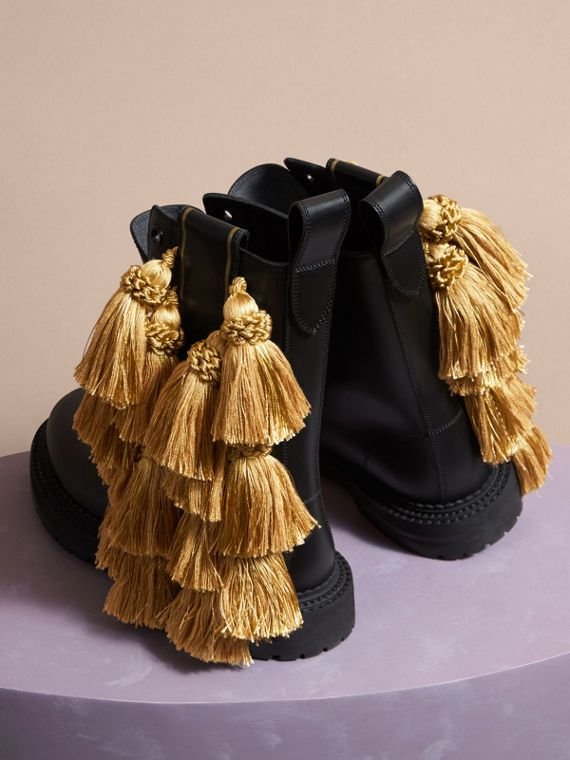 Mid-calf, lace-up army boots in matt-finish calf leather from Burberry. The handmade tassels nod to the regimental mood in the collection.