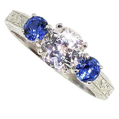 White sapphire with blue diamond side stones