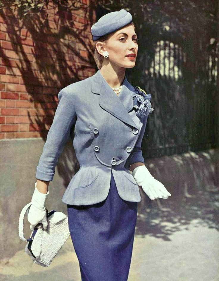 Geneviève in summer suit of lilac and purple linen, the curved jacket has a bib front by Pierre Balmain, straw purse by Violette Cornille, jewelry by Francis Winter, photo by Pottier, 1954