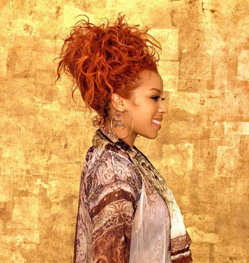 Keyshia Cole with red curly hair gathered in a top bun. on The Fashion Time  http://thefashiontime.com/15-keyshia-cole-best-hairstyles/#sg15