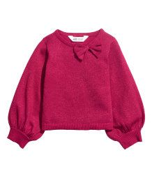 Fine-knit sweater in a soft cotton blend with glittery threads. Attached bow at top and long balloon sleeves with narrow ribbing at cuffs.
