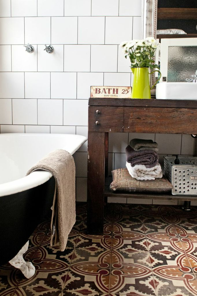 Bring bohemian style to a boring white bathroom with cement encaustic tiles in warm reds and browns.