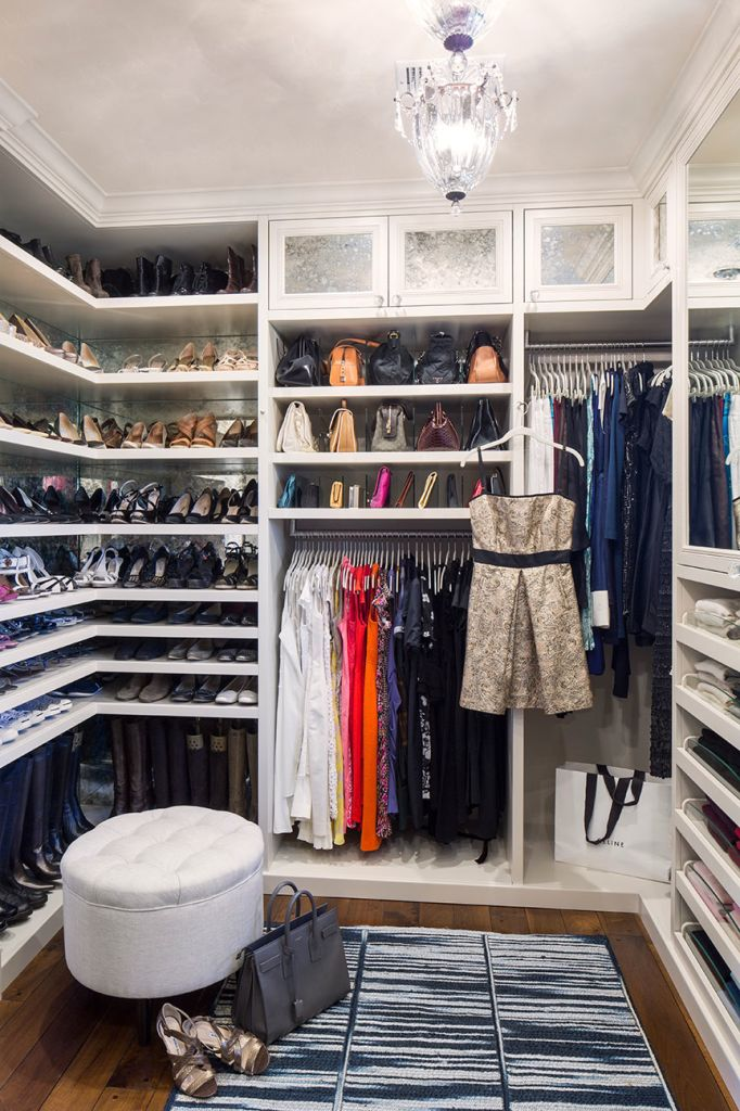 gorgeous closet features floor to ceiling shelves for shoes as well as bottom rack used to hang boots accented with antiqued mirrored backsplash